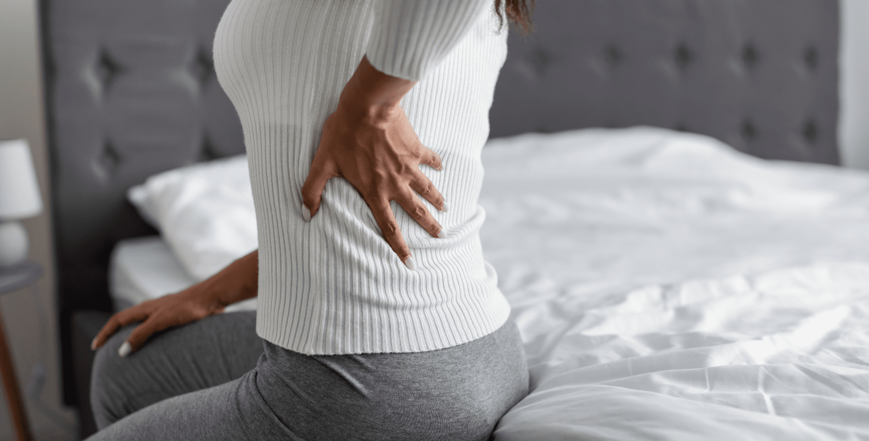woman-with-side-back-pain-sitting-on-bed-at-home-H@3x